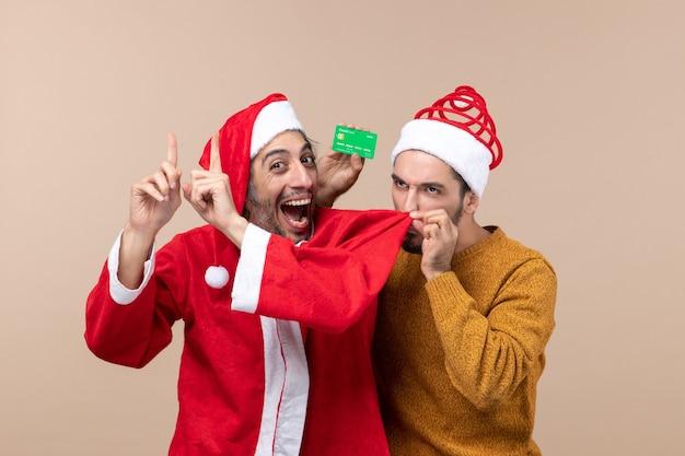 正面図2人のクリスマスの男1人はサンタのコートを着ており、もう1人はベージュの孤立した背景に友達のコートの匂いを嗅ぐクレジットカードを持っています