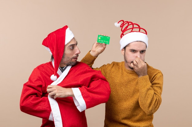 Front view two xmas guys one with santa coat and the other with credit card closing his nose on beige isolated background