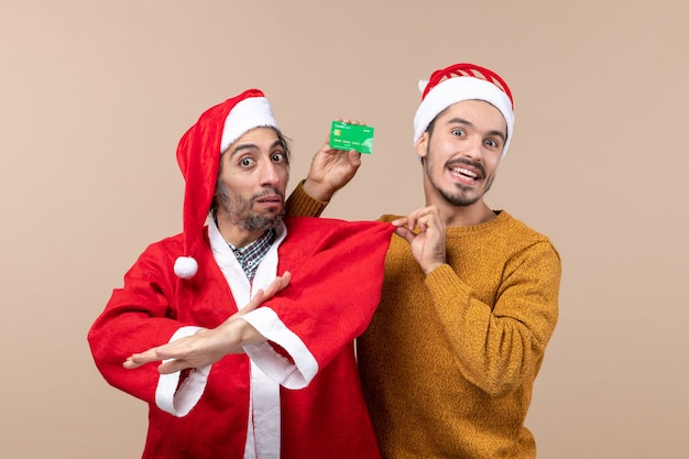 Front view two xmas guys one with santa coat and the other with credit card pulling his friends coat on beige isolated background