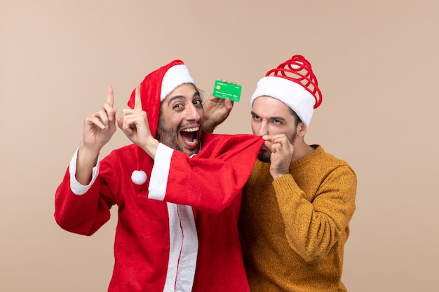 Front view two xmas guys one with santa coat and the other with credit card smelling his friends coat on beige isolated background