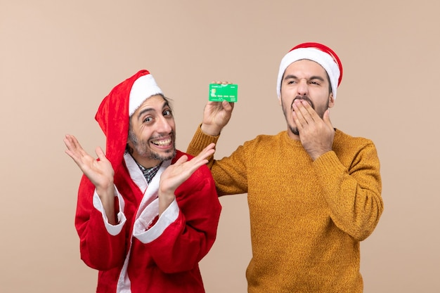 Front view two xmas guys one with santa coat and the other with credit card yawning on beige isolated background