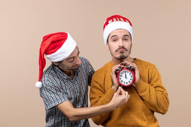 Vista frontale due uomini di natale uno che tiene una sveglia con entrambe le mani e l'altro che mostra il tempo su fondo isolato beige