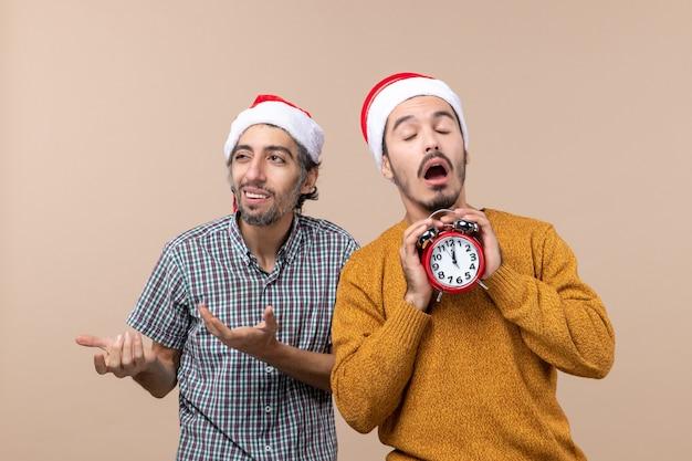 Vista frontale due uomini di natale uno in possesso di una sveglia con gli occhi chiusi su sfondo beige isolato