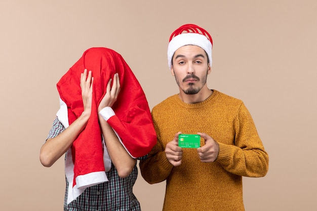 Front view two xmas men one holding credit card and the other covering his head with santa coat on beige isolated background