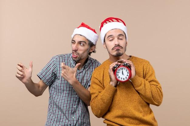 눈 깜박임과 베이지 색 격리 된 배경에 닫힌 눈으로 알람 시계를 들고 다른 하나는 전면보기 두 크리스마스 남자