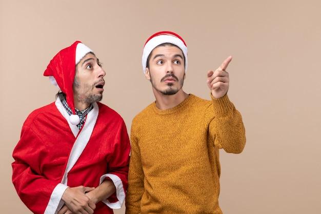 Vista frontale due giovani uomini entrambi guardando da qualche parte su sfondo beige isolato