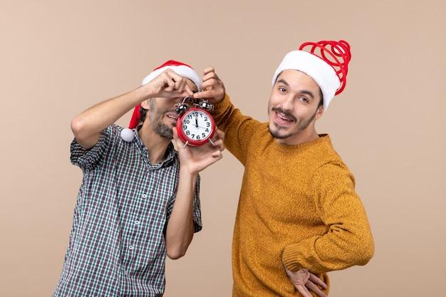Vista frontale due giovani uomini che tengono sveglia rossa su sfondo beige isolato