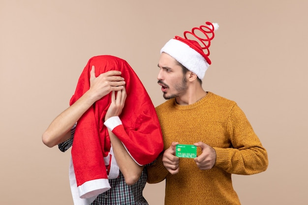 Front view two young men one holding credit card and the other covering his head with santa coat on beige isolated background