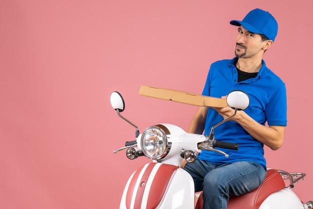 Vista frontale di un corriere incerto e incerto che indossa un cappello seduto su uno scooter che tiene l'ordine su sfondo color pesca pastello