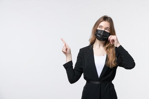 Vista frontale di una giovane donna incerta e incerta in tuta che indossa una maschera chirurgica e punta verso l'alto su bianco