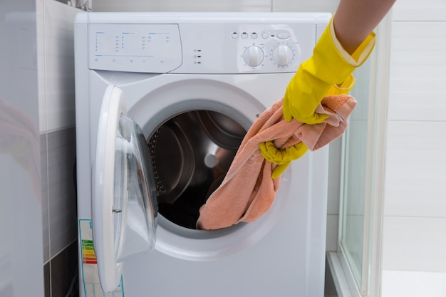 Front view of unidentifiable yellow rubber gloved hand pulling pink towel out of small front loading washing machine