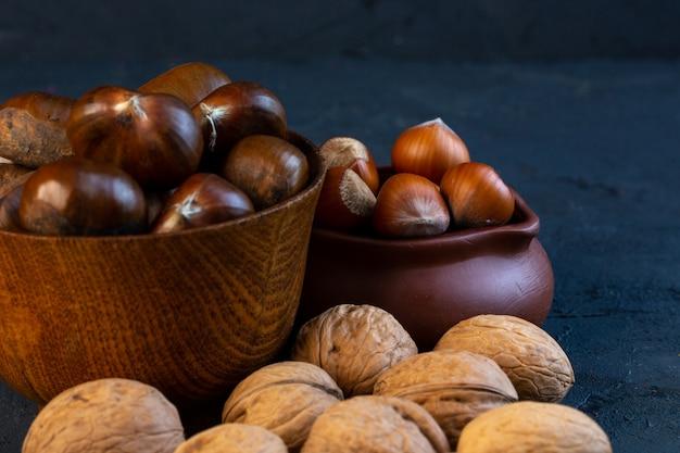 Вид спереди неочищенных каштанов в чашке с неочищенными орехами и грецкими орехами