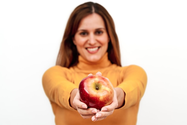Front view of unrecognizable woman out of focus showing an apple in her hands.