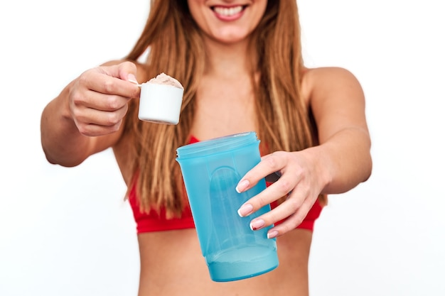 Front view of unrecognizable woman preparing a protein shake to drink after workout.