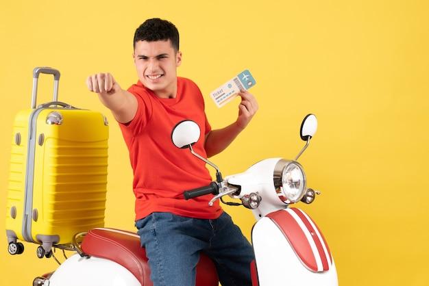 Вид спереди неудержимого молодого мужчины в повседневной одежде на мопеде с билетом