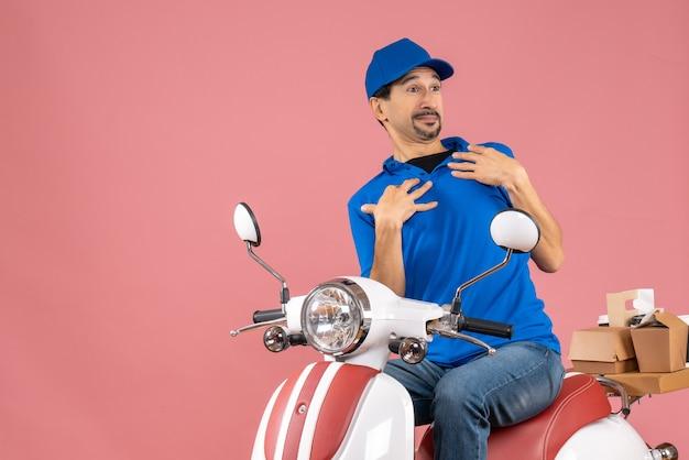 Vista frontale del ragazzo delle consegne incerto che indossa un cappello seduto su uno scooter che si punta su sfondo color pesca pastello