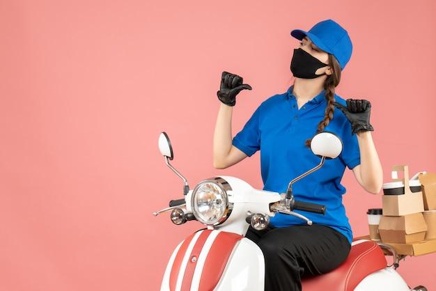 Vista frontale di una ragazza corriere incerta e incerta che indossa maschera medica e guanti seduti su uno scooter che consegna ordini su sfondo color pesca pastello
