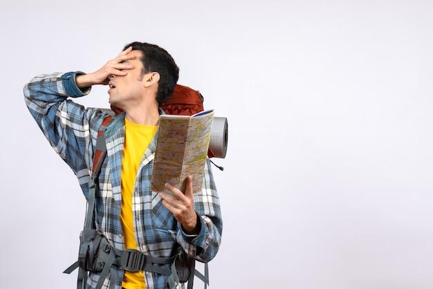 Вид спереди расстроен молодой путешественник с рюкзаком, держащим карту