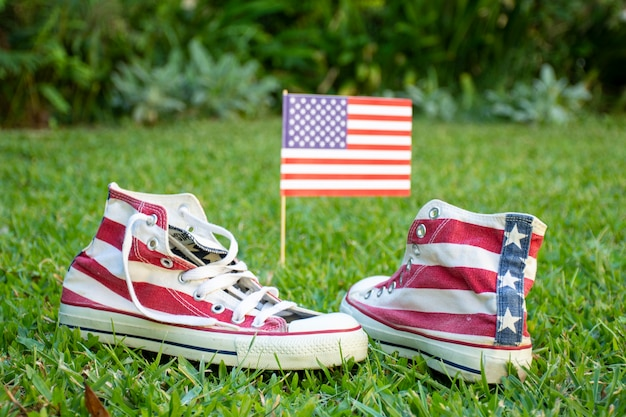フロントビュー米国旗とスニーカーの芝生の上