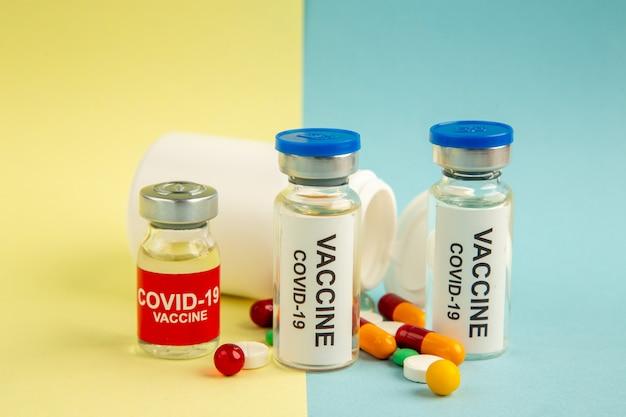 黄青色の背景にさまざまな錠剤を含むcovidに対する正面ワクチン