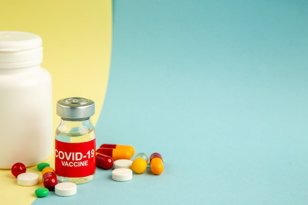 Front view vaccine against covid with different pills on yellow-blue background
