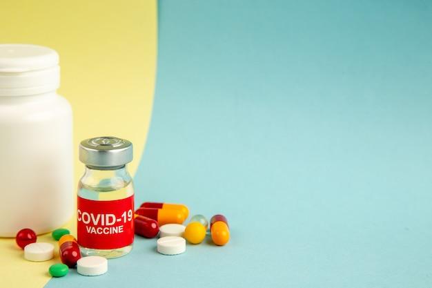 Vista frontale vaccino contro covid con diverse pillole su sfondo giallo-blu