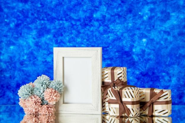 Vista frontale regali di san valentino fiori cornice bianca riflessa sullo specchio su sfondo blu sfocato
