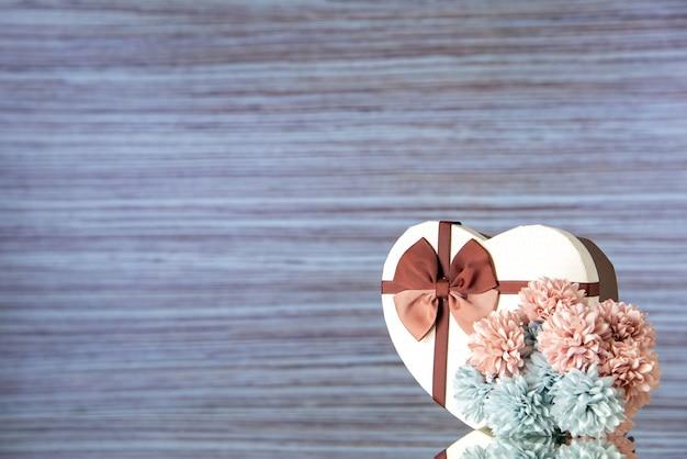 Vista frontale regalo di san valentino con fiori su sfondo chiaro colore amore passione coppia cuore sentimento famiglia bellezza spazio libero