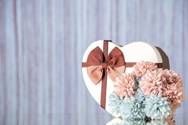 Vista frontale regalo di san valentino con fiori su sfondo chiaro colore amore passione coppia cuore sentimento famiglia bellezza