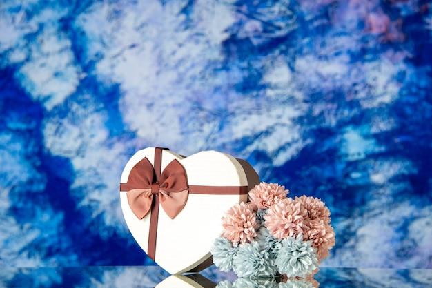 Vista frontale regalo di san valentino con fiori su sfondo azzurro amore famiglia matrimonio sensazione bellezza nuvola colore passione amante
