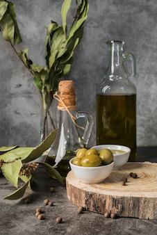 Vista frontale varietà di olio d'oliva e olive