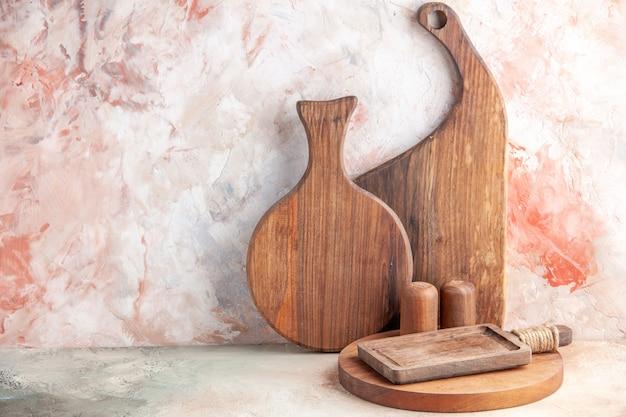 Vista frontale di vari tipi di taglieri in legno in piedi su una superficie colorata