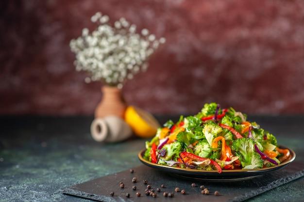 Vista frontale dell'insalata vegana con ingredienti freschi in un piatto e pepe su tagliere nero