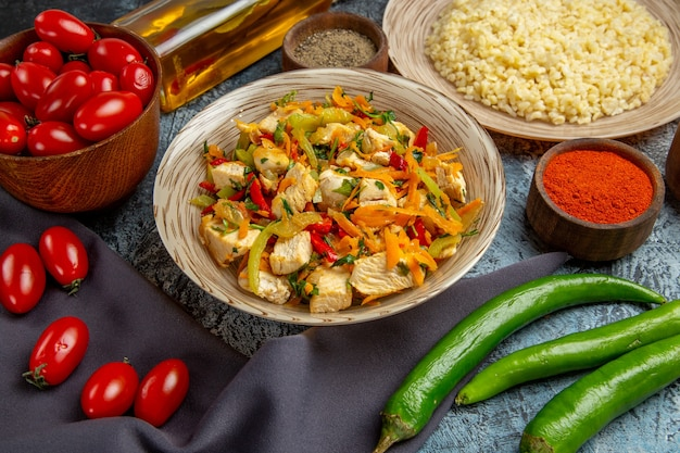 Vista frontale di insalata di pollo vegetale con pomodori sulla superficie chiara