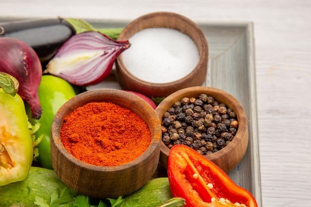 Vista frontale composizione vegetale con verdure e condimenti sullo sfondo bianco colore dieta foto pasto maturo vita sana insalata