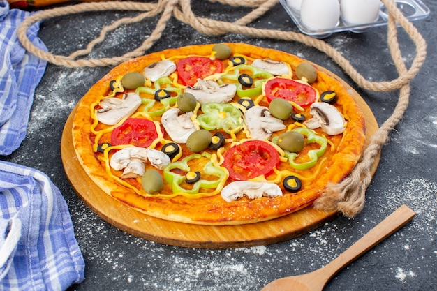 Front view vegetable mushroom pizza with tomatoes olives mushrooms with flour on grey desk pizza dough italian food