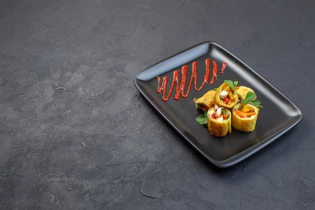 Овощные паштеты, вид спереди, внутри черной тарелки на темной поверхности
