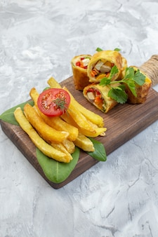 Il patè di verdure di vista frontale rotola con le patatine fritte sulla superficie bianca