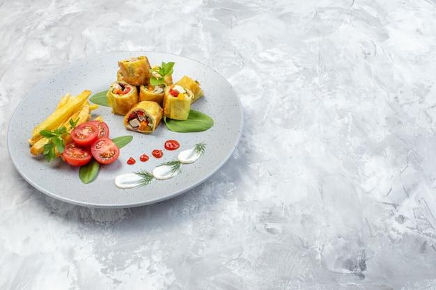 Il patè di verdure di vista frontale rotola con i pomodori e le patatine fritte all'interno del piatto sulla superficie bianca