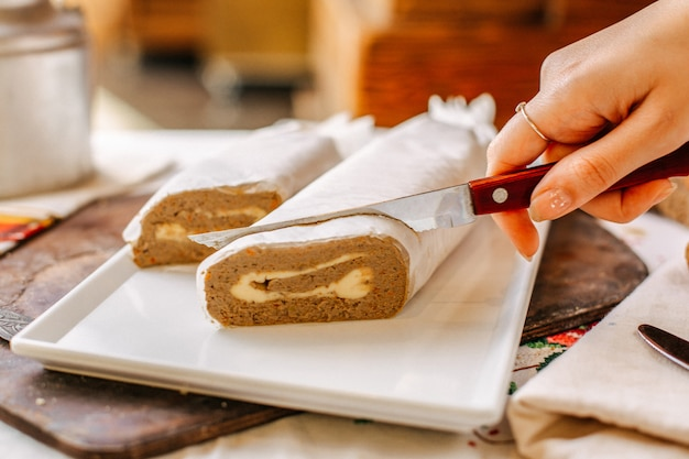 A front view vegetable pate tasty salted getting sliced by woman inside white plate rolls meal