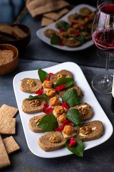 Un patè di verdure di vista frontale con le foglie verdi delle noci insieme ai prodotti del pasto del vino rosso delle patatine fritte sullo scrittorio grigio