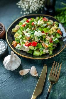 Vista frontale insalata di verdure è composta da cetriolo formaggio e pomodori su sfondo blu scuro