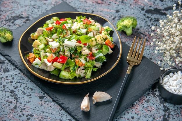 正面図の野菜サラダは、暗い背景のプレート内のキュウリチーズとトマトで構成されています