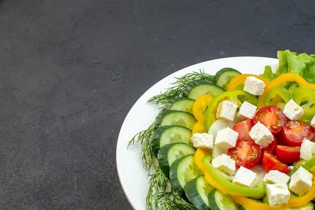 正面図の野菜サラダは、暗い背景にスライスしたキュウリ、トマト、コショウ、チーズで構成されています