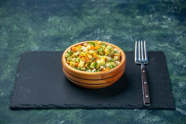 어두운 배경에 작은 접시 안에 삶은 재료에서 전면보기 야채 샐러드