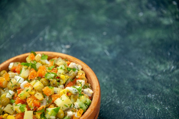 Овощной салат из вареных овощей, смешанный внутри круглой тарелки на темном фоне, вид спереди