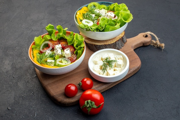 暗い背景にチーズきゅうりとトマトの正面野菜サラダ