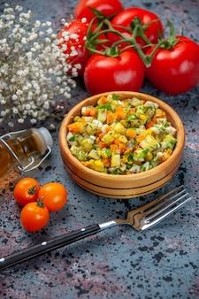 밝은 파란색 배경에 포크와 토마토와 전면보기 야채 샐러드