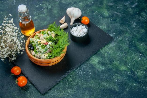 Овощной салат с зеленью и чесноком на синем фоне, вид спереди