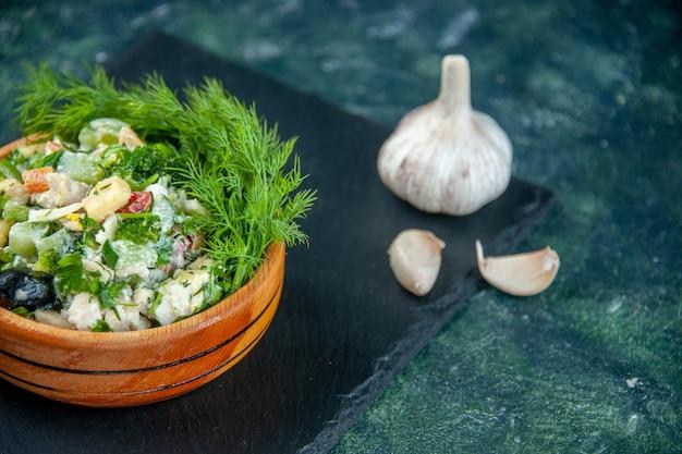 Insalata di verdure vista frontale con verdure all'interno pentolino su sfondo blu scuro